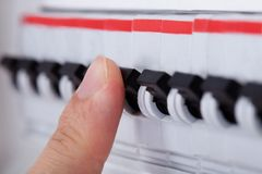 Human hand on distribution board. Close-up Of Hand On Switch Of Distribution Board royalty free stock image
