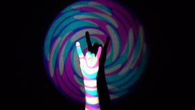 The human hand doing horns sign with his fingers on background of colorful tunnel flythrough loop.  stock video footage