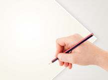 Human hand drawing with pencil on empty paper template Stock Photos