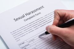 Human Hand Filling Sexual Harassment Complaint Form. Close-up Of A Human Hand Filling Sexual Harassment Complaint Form With Pen stock image