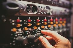 Human hand fine tuning levels on professional audio equipment. Macro close up of vintage sound studio audio equipment control panel knobs and levels human hand stock image