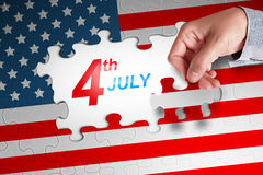 Human hand finishing a american flag puzzle with Fourth 4th of J Stock Image