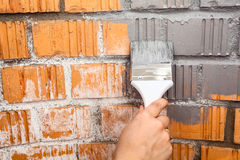 Human hand with grey colored brush painting brick wall Stock Photo