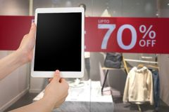 Human hand hold blank screen smart phone, tablet, cellphone on. Discount label at cloth store background. concept of online shopping stock photo