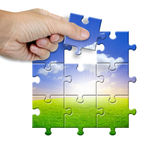 Human hand hold a piece of landscape jigsaw Stock Image