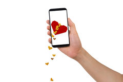 Human hand hold smartphone with blank screen and red broken heart icon with falling hearts. Royalty Free Stock Images