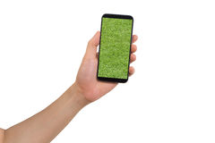 Human hand hold  smartphone with grass field on screen. Stock Photos