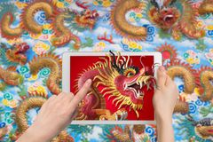 Human hand hold smartphone, tablet, cell phone with big dragon s. Tatue come out screen. concept of celebrate Chinese New Year background , concept of the Year Stock Photography