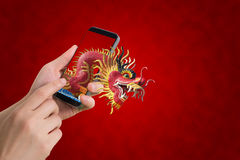 Human hand hold smartphone, tablet, cell phone with big dragon s Royalty Free Stock Photos