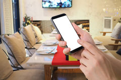 Human hand hold smartphone, tablet, cell phone on blurry kitchen Royalty Free Stock Image