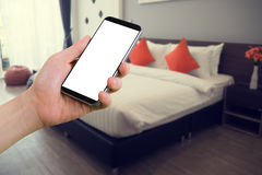 Human hand hold smartphone, tablet, cell phone with blurry moder. N bedroom. concept of  finding hotel Royalty Free Stock Photos