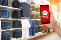 Human hand hold smartphone, tablet, cell phone with shop cart on Royalty Free Stock Image