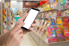 Human hand hold and touch blank screen smart phone, tablet, cellphone on blurry bookshelf in bookstore Royalty Free Stock Photo