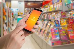 Human hand hold and touch screen on smart phone with virtual app e-book over bookshelf. Online shopping Concept Royalty Free Stock Photo