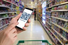 Human hand hold and touch smart phone, tablet, cellphone with QR. Code number on products shelf store. concept of shopping online stock image