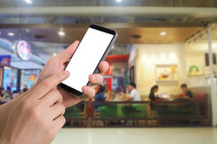 Human hand hold and touch smartphone with blank screen on blurred people eating at food court background. Stock Photos