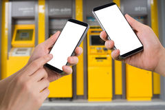 Human hand hold and touch smartphone, tablet, cell phone with blank screen, virtual internet banking on blurry cash machines backg Royalty Free Stock Photos