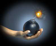 Human hand holding a bomb with burning fuse. Human hand holding a bomb with burning fuse, on dark background Royalty Free Stock Image