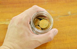 Human hand holding bottle of gold coin on table Royalty Free Stock Image