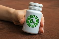 Human hand holding a bottle of pills with vitamin B12 Royalty Free Stock Images