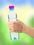 Human hand holding a bottle of water over blurred natural Stock Photography