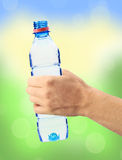 Human hand holding a bottle of water over bright nature. Background Royalty Free Stock Photo