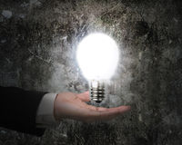 Human hand holding brightly light bulb illuminated dark old wall. Background Royalty Free Stock Photo