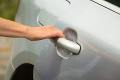 Human hand holding car door handle Royalty Free Stock Image