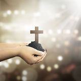 Human hand holding christian cross with soil on the hand. Over blur background Royalty Free Stock Image