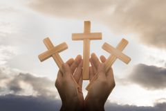 Human hand holding a cross, the background is the sunrise., Concept for Christian, Christianity, Catholic religion, divine, heave royalty free stock photography