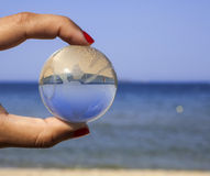 Human hand holding crystal globe. Stock Images