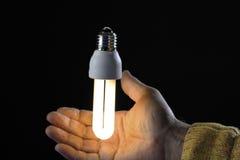 Human hand holding energy saving lamp, close-up Stock Photos
