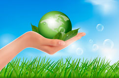Human hand holding green globe with leaves. Stock Image
