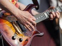 Human hand holding guitar music instrument. Musician or guitarist playing guitar string music instrument Royalty Free Stock Images