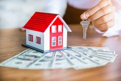 Human hand holding key of model house.  Real estate and residential concepts, house trading stock photos