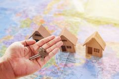 Human hand holding key of paper house toy or cardboard house on. Selective focus - Human hand holding key of paper house toy or cardboard house on world map with Stock Photos