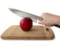 Human hand holding a knife and a red apple royalty free stock image