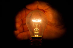 Human hand holding a light bulb to conserve energy darkness Stock Photo