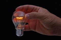 Human hand holding a light bulb to conserve energy darkness Stock Photos