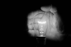 Human hand holding a light bulb to conserve energy darkness arti Stock Photography