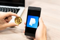 Human hand holding mobile phone and Bitcoin coin - paypal logo displayed on phone,, computer laptop in the background stock photo