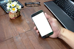 Human hand holding mobile smart phone and office equipment on de Stock Photo