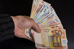 Human hand holding money-euro banknotes isolated on a dark gray background. Human hand holding money - fifty-twenty-ten euro banknotes isolated on a dark gray Stock Photography