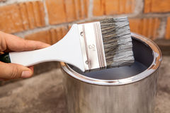 Human hand holding paint brush stained grey color Stock Photos