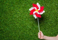 Human hand holding pinwheel over grass Royalty Free Stock Photo