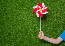 Human hand holding pinwheel over grass Royalty Free Stock Image