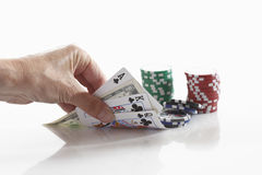 Human hand holding playing cards with gambling chips Stock Photography