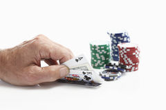 Human hand holding playing cards with gambling chips Royalty Free Stock Photos
