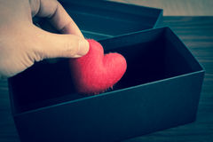 Human hand holding or putting a red heart-shaped in a black gift Stock Photography