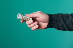 Human hand holding rolled up paper dollar currency.  Royalty Free Stock Image